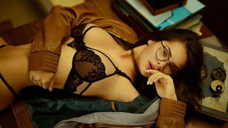 Брюнетка в нижнем белье в очках лежит на спине
