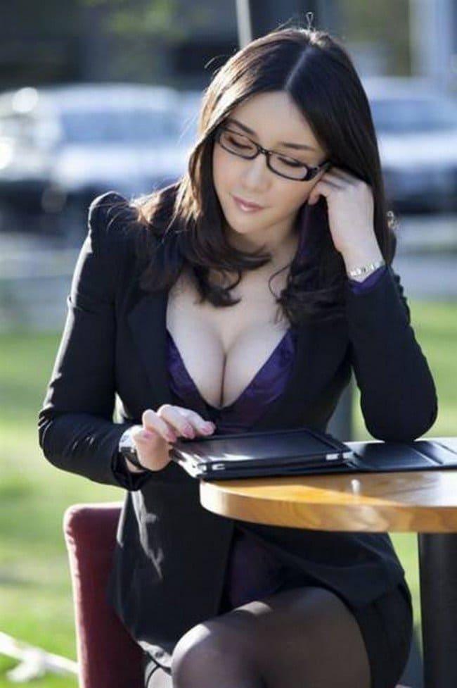 Красивая брюнетка в очках сидит за столом, сиськи выпадают с платья