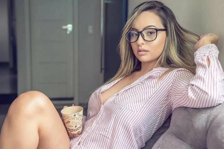 Блондинка полусидит в кресле в рубашечке растегнуьой