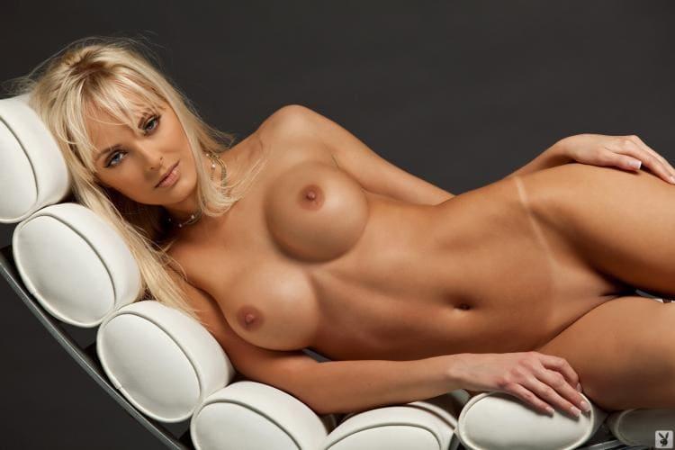 Красивая блондинка голая без трусов лежит на боку, сиськи