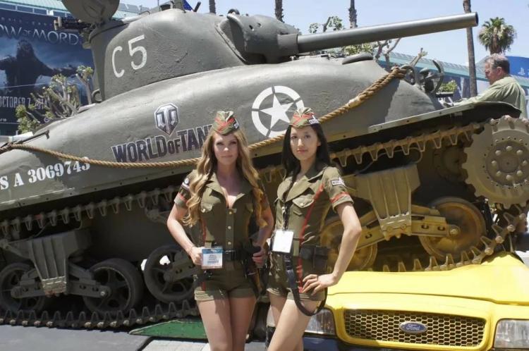 Две девушки в коротеньких шортах в пилотках стоят возле танка