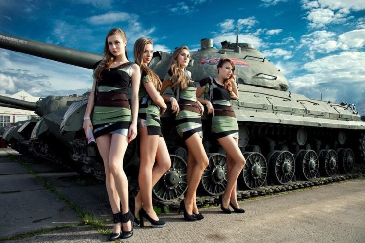 Четыре красотки в коротких платьях стоят возле танка