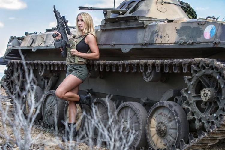 Стоит возле танка в коротких шортах с автоматом в руках