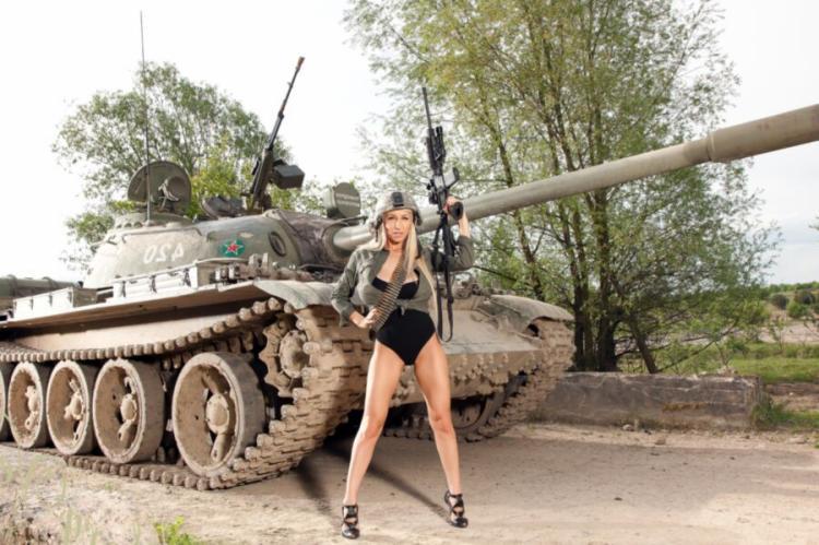 В сплошном черном купальнике стоит возле танка раставивив ноги