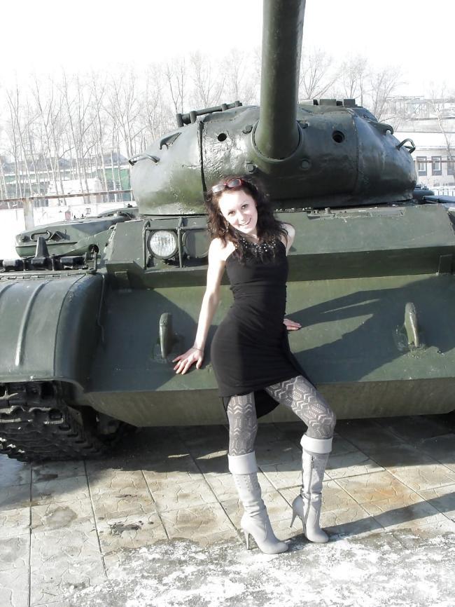 В коротком черном платье в плотных колготках сапожках стоит возле танка