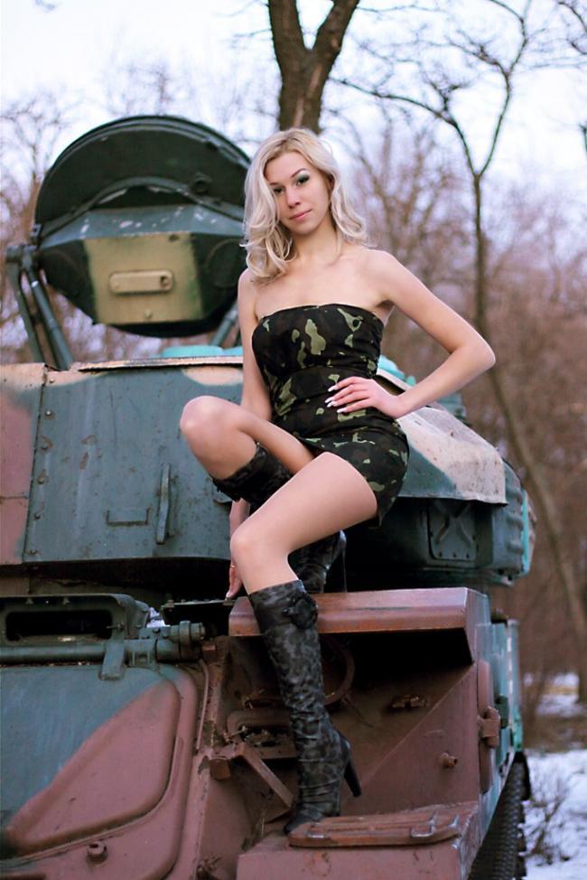 Блондинка в коротком платье в сапожках сидит на танке