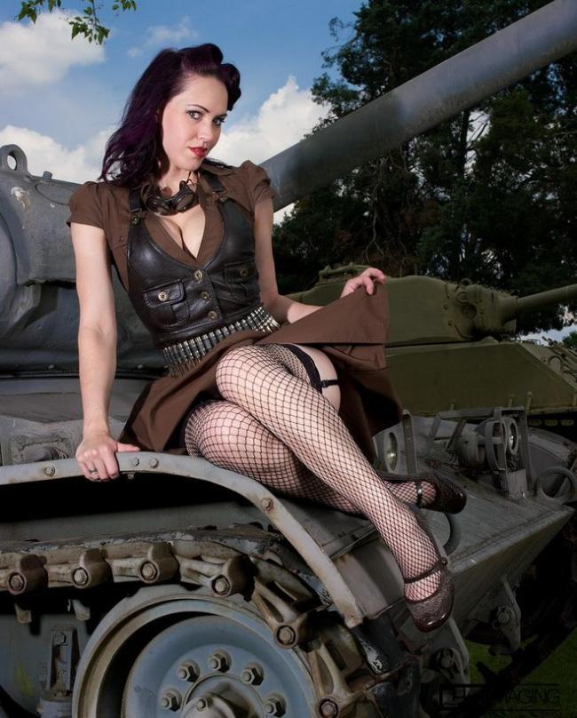 Красивая брюнетка сидит на танке подняв юбку, обнажив ножки в чулочках в крупную сетку