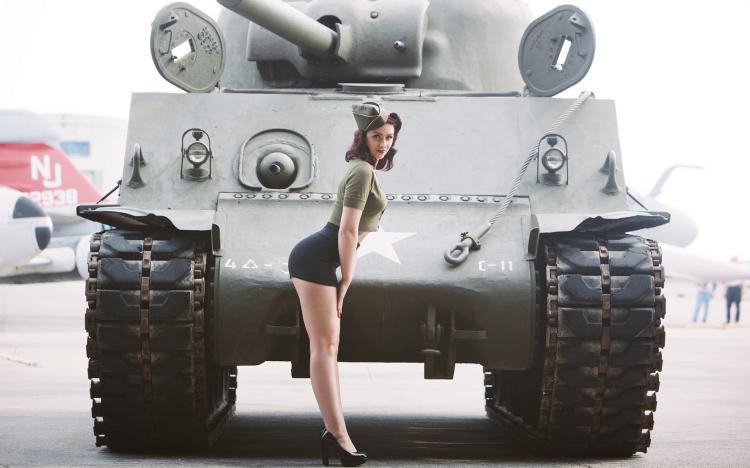 В коротенькой черной юбке на каблуках возле танка
