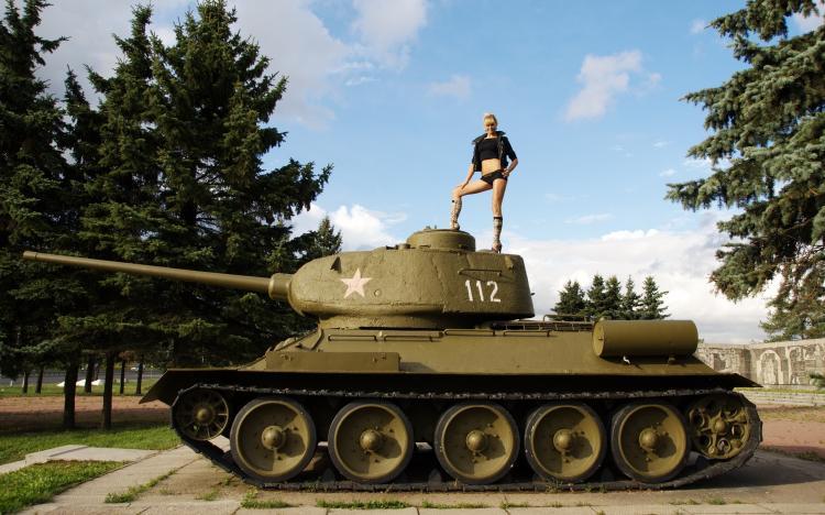 Стоит на башне танка в коротких шортах ножки