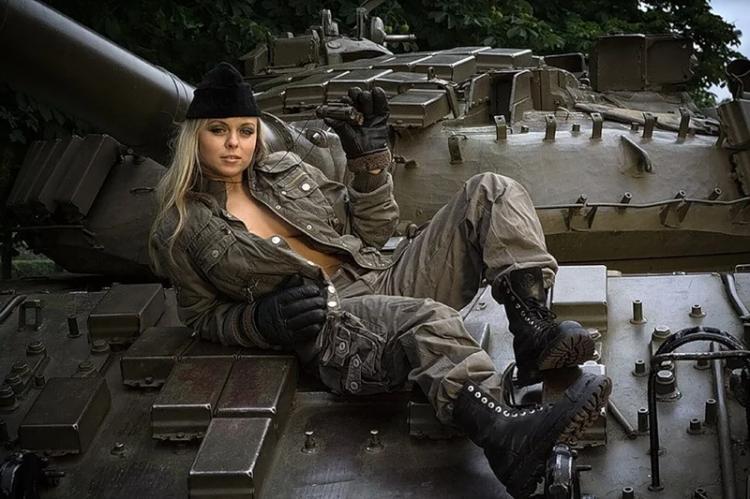 Красивая блондинка в рабочем комбинезоне сексуально расстегнутом полулежит на танке