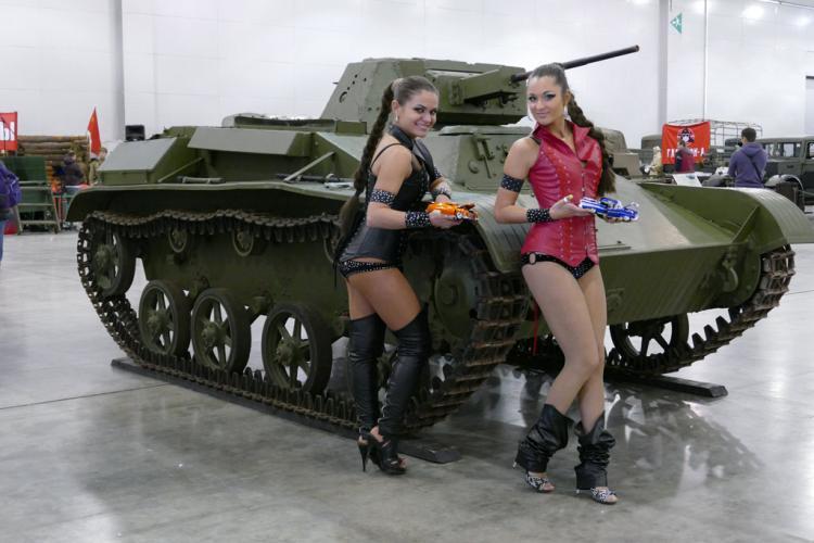 Две полуобнаженные красивые девушки возле танка стоят