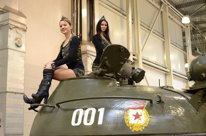 Две девушки в пилотках в саожках в коротких юбках сидят на танке
