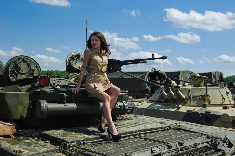В коротком платье хамелеон на каблуках сидит на танке