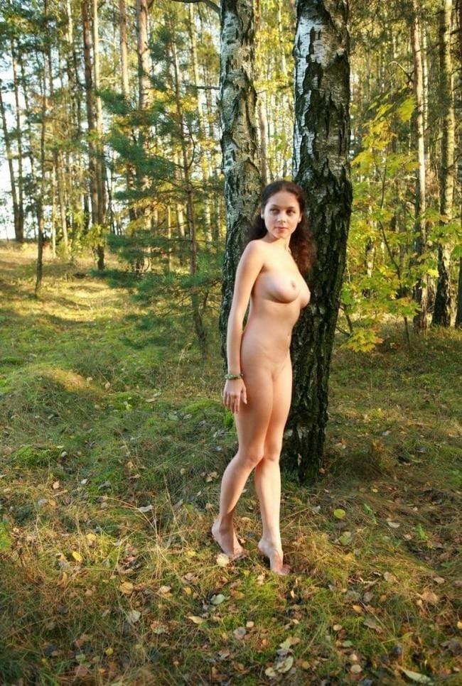 Голая девушка стоит возле дерева, вид сбоку