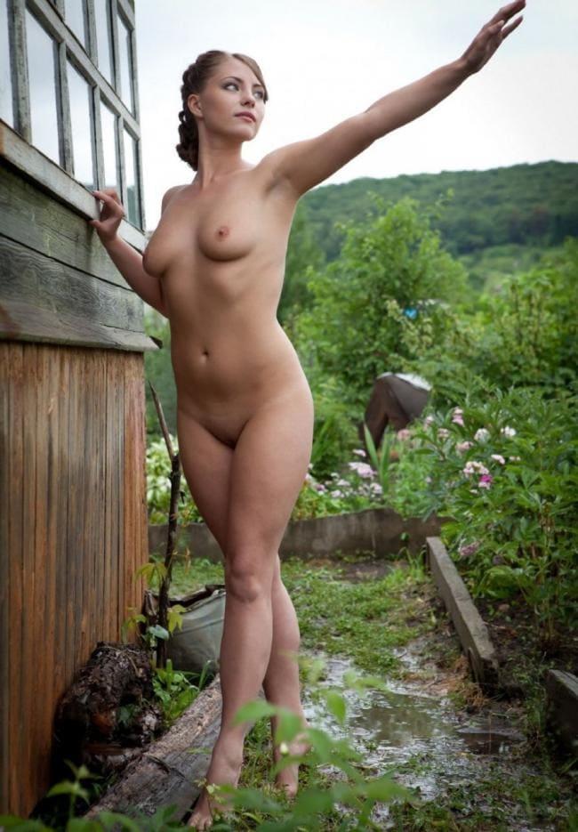 Голая красивая девушка стоит на цыпочках подняла руку