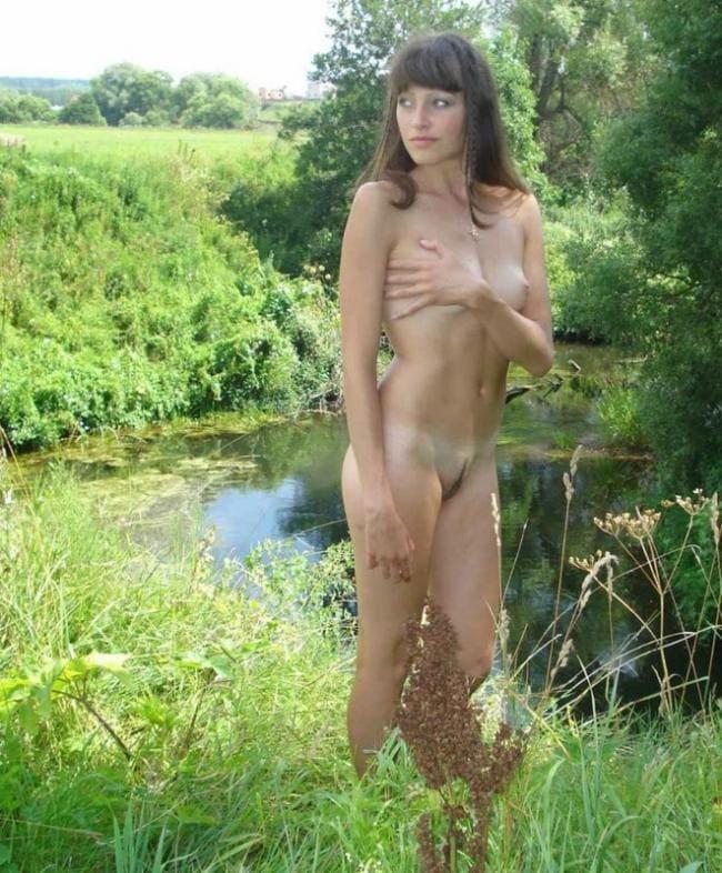 Голая стоит возле пруда прикрывая рукой маленькую грудь