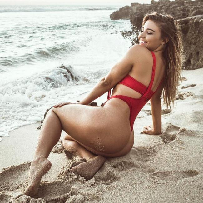 фото Jem Wolfie в красном купальнике сидит на песке, вид сбоку