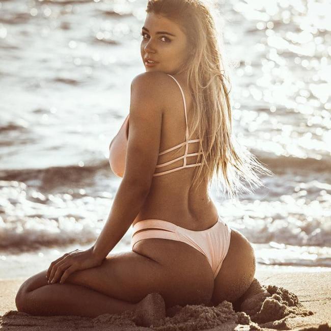 фото Jem Wolfie сидит на коленях на песчаном берегу моря в предрассветных лучах солнца в розовом купальнике, вид сбоку