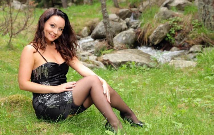 Карла Браун сидит на траве в открытом черном платье чулках