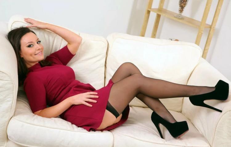 Карла Браун в красном задранном платье полулежит на белом диване, чулки каблук