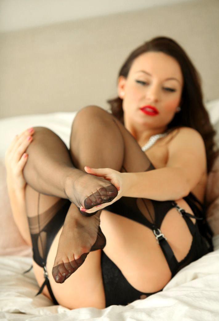 Карла Браун в чулках на поясе лежит на кровати и показывает ступни, губы накрашены ярко-красной помадой, волосы забраны назад