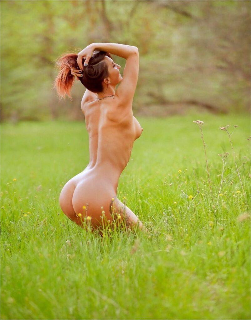 фото голых девушек на природе на зеленом лугу немного согнув ноги в коленях стоит подняв руки на голову и собрав волосы в хвост вид сбоку