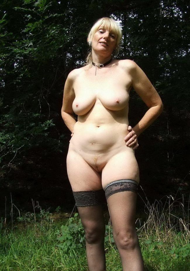 Голая зрелая блондинка в чулках стоит на поляне