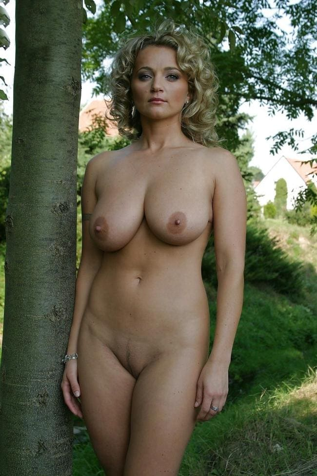 Красивая голая зрелая женщина стоит на природе