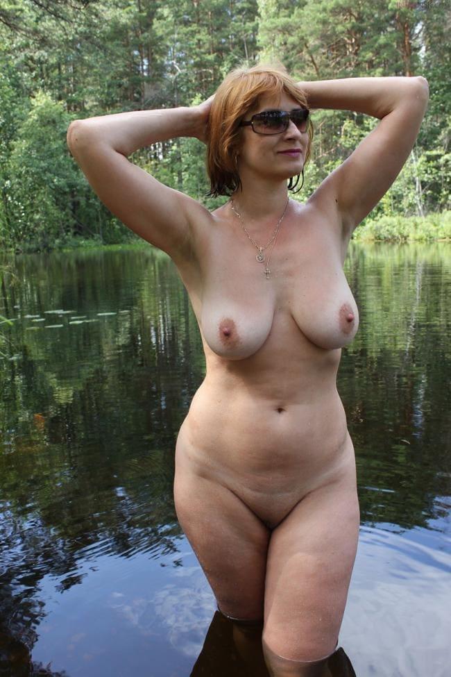 Голая зрелая на природе в пруду стоит по колено в воде демонстрируя голую грудь подняв руки на затылок