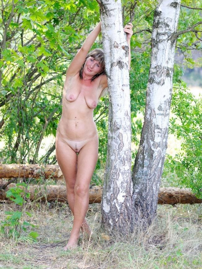 Голая русская зрелая с хорошей фигурой висячими сиськами стоит у березы подняв руки