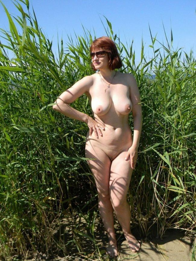 Зрелая голая с красивой фигурой и обнаженными сиськами в очках стоит в камышах на песчаном берегу