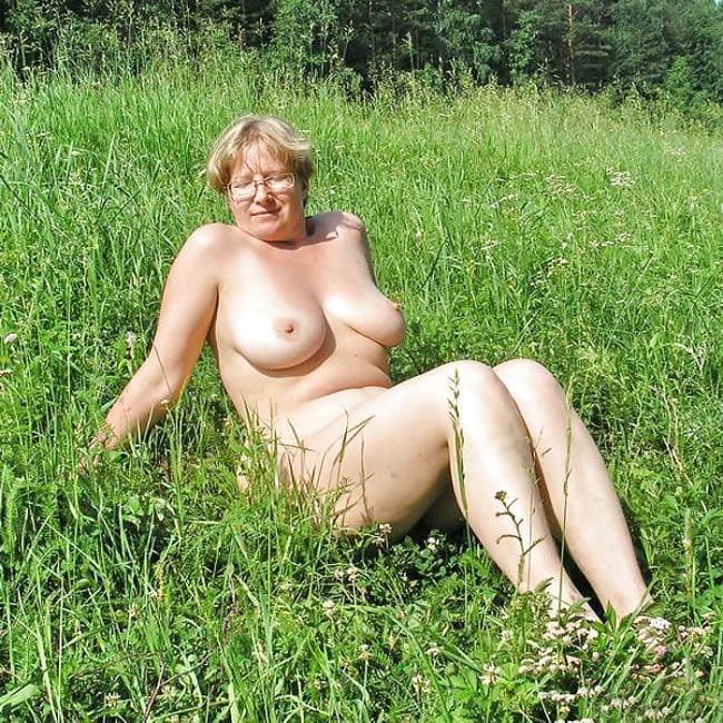 Голая зрелая блондинка в очках сидит на попе среди травы в поле