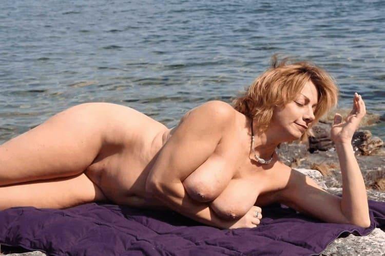 Красивая голая зрелая блондинка нежится на солнышке на берегу моря