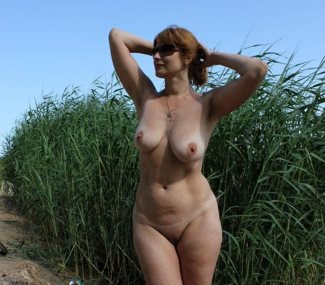 Красивая голая зрелая тетя с прекрасной фигурой стоит на берегу реки в камышах, руки подняла на голову