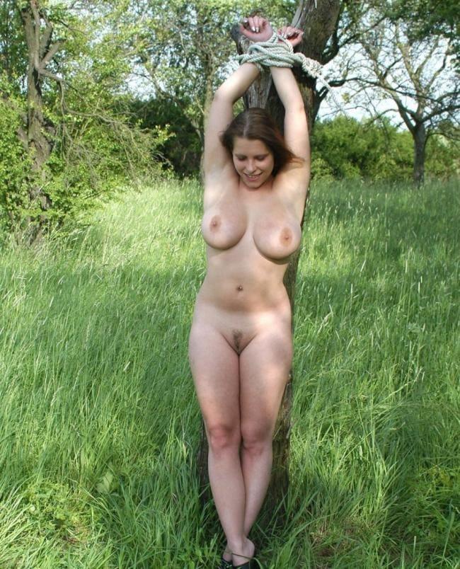 красивая зрелая женщина привязана веревкой к дереву на опушке леса, сиськи торчат на пизде интимная стрижка, мило улыбается