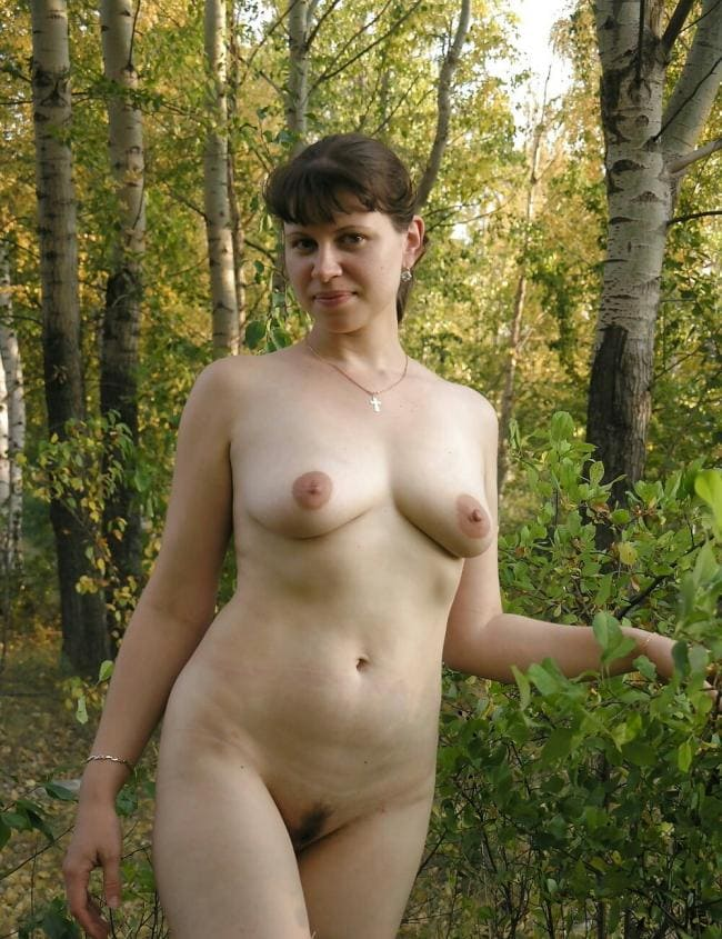 красивая зрелая женщина в лиственном лесу абсолютно голая, сиськи торчком, пизда аккуратно подстрижена, повернула голову и мило улыбается, на правой руке браслет