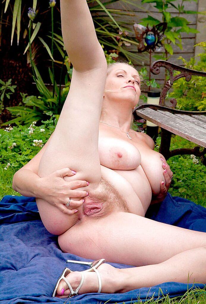 Фото голых зрелых женщин на природе лежит на траве рядом с лавочкой, правую ногу подняла и правой же рукой раздвигает небритую пизду, левая нога согнута в колене на ней надеты туфли на высоком каблуке, облокатилась на локоть левой руки и придерживает грудь.
