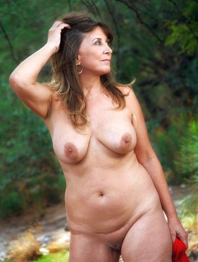 Зрелая женщина на природе гуляет голая сзади течет ручей, поправляет длинные распущенные волосы рукой, пизда бритая