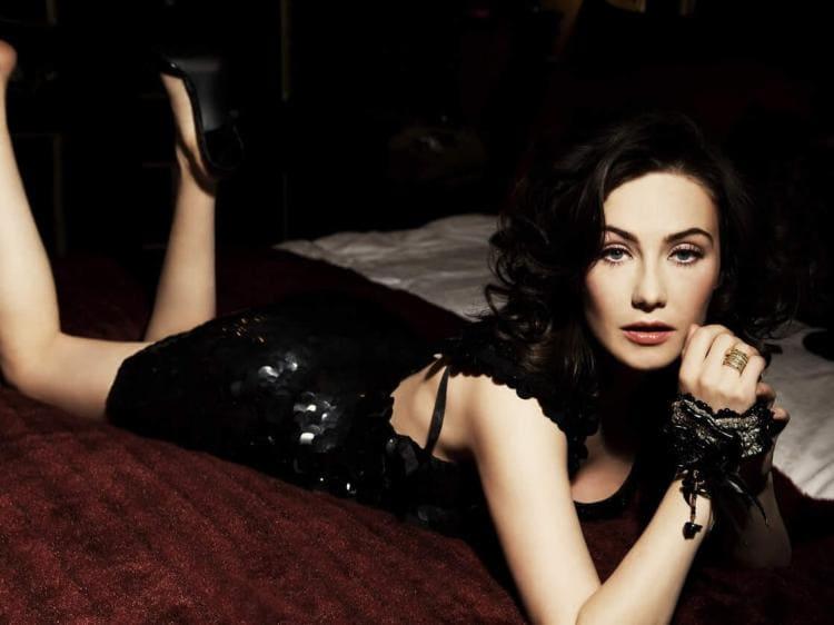 Лежит на животе в короткеом сексуальном черном платье, ножки туфли