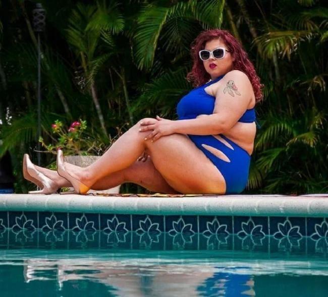 Фото толстая женщина в сплошном купальнике сидит возле бассейна