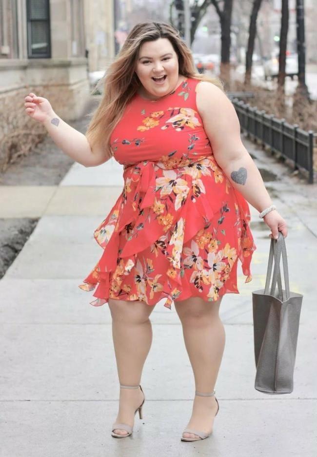Красивая толстая девушка в коротком шифоновом платье красного цвета и серой сумкой танцует на улице