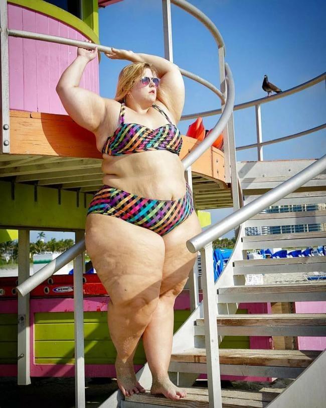 Фото толстая женщина блондинка стоит в купальнике подняв руки на спиральной лестнице