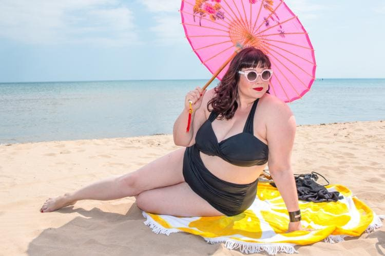 Фото толстая красивая женщина в очках в купальнике на морском песчаном пляже под розовым зонтиком от солнца, в солнечных очках