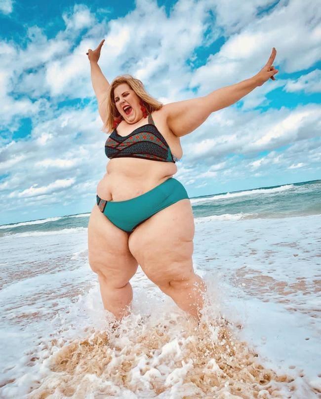 Толстая женщина в купальнике подняла руки открыла рот живот большие ляжки
