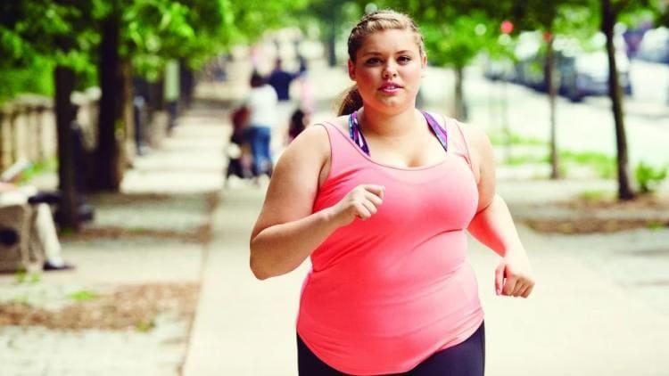Толстая девушка в маечке спортом занимается