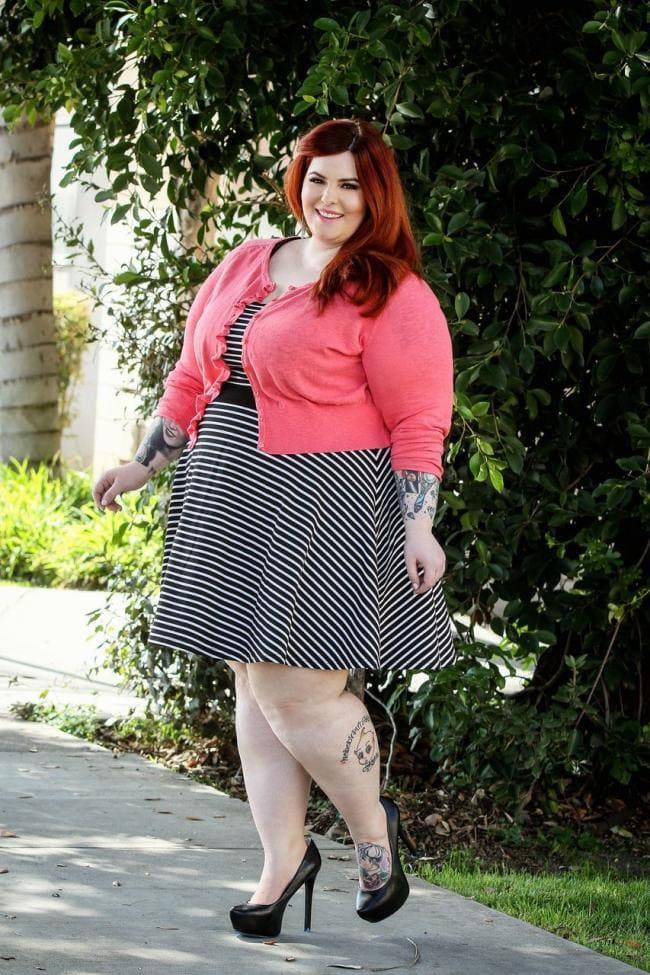 Очень толстая красивая девушка стоит, тату на руках и ноге