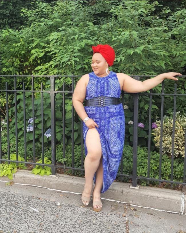 Толстая женщина стоит сексуально подняв платье оголив ножку