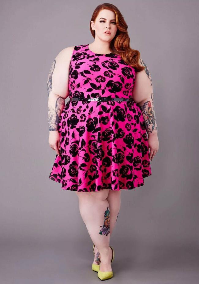 Очень толстая красивая девушка в платье стоит