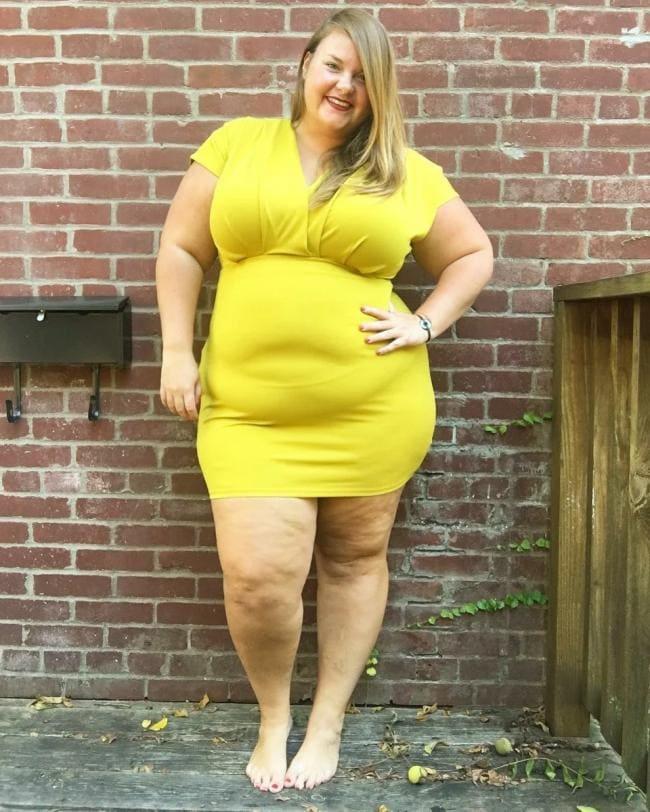 Фото женщин толстая блондинка в коротком желтом платье стоит у кирпичной стены