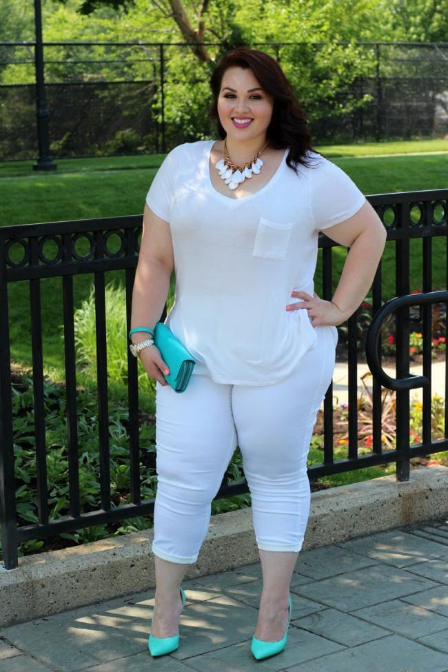 Фото красивая толстая женщина в белых бриджах и футболке стоит